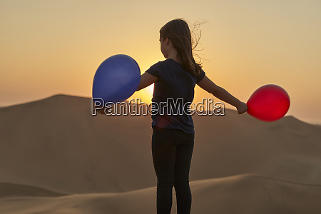 girl playing with balloons in the