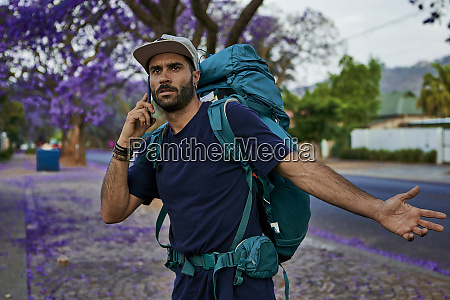 backpacker steht mit seinem smartphone auf