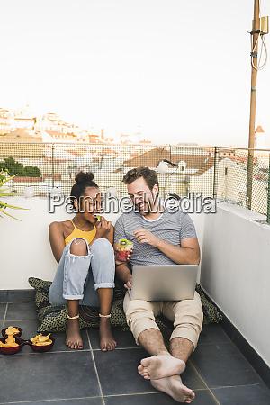 glueckliches junges paar mit laptop sitzt
