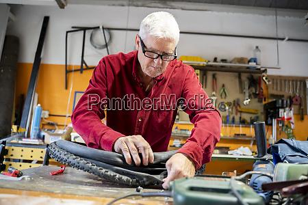 senior mann repariert fahrradreifen in garage