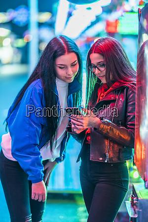 zwei teenager maedchen teilen smartphone auf