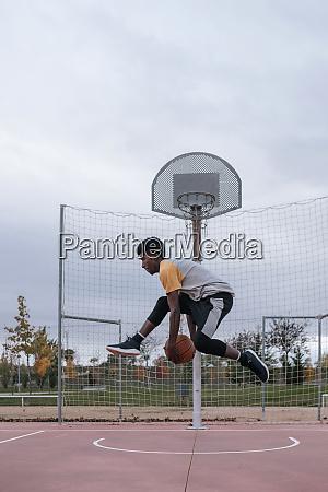 teenager spielt basketball