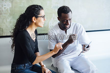 dentist with tablet speaking with female