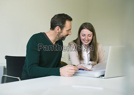 geschaeftsmann und mitarbeiter mit laptop und