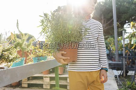 junge mit topfpflanze in pflanzengaertnerei