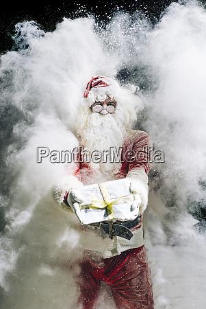 weihnachtsmann zeigt geschenk