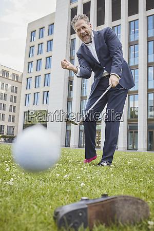gluecklicher reifer geschaeftsmann spielt golf auf