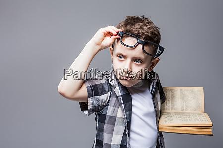 smarter schueler in brille mit lehrbuch