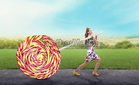 girl drags a huge colorful candy