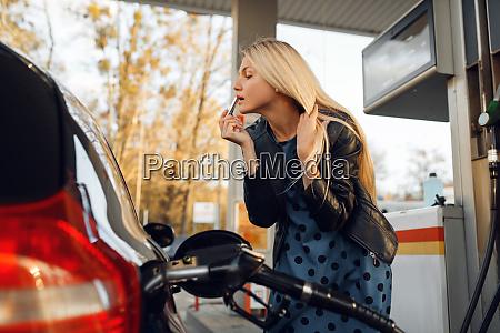 frau befeuert fahrzeug auf tankstelle tankfuellung