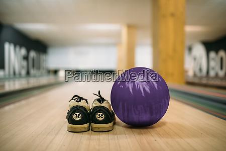 bowlingball und hausschuhe auf bahn nahaufnahme