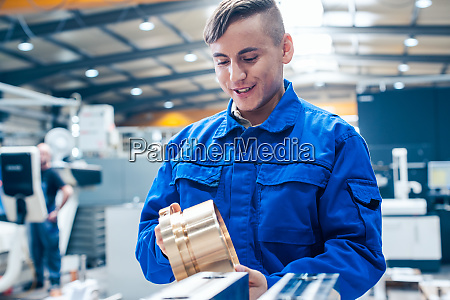 lehrling in der metallbearbeitung mit werkstueck