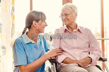 betreuerin mit seniorin im altenheim