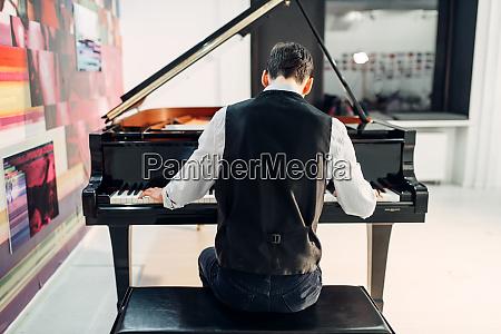 maennlicher pianist spielt komposition am fluegel