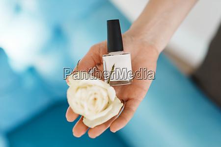 frau haelt nagellack und eine blume