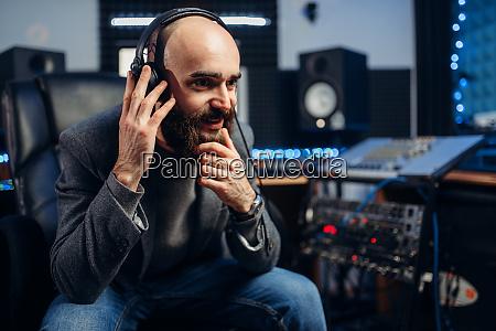 soundproduzent in kopfhoerern hoert komposition