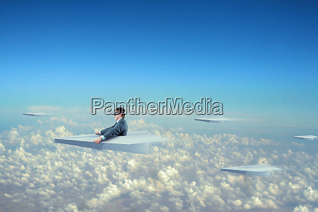 geschaeftsmann fliegt mit papierflugzeug