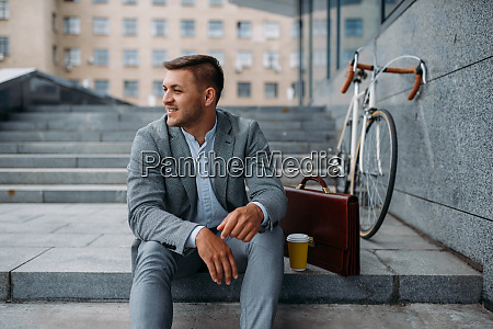 geschaeftsmann mit fahrrad beim mittagessen im