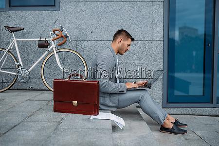 geschaeftsmann mit fahrrad und laptop beim