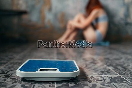anorexische frau sitzt auf dem boden