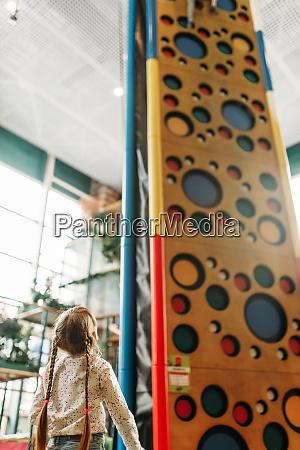 kleines maedchen schaut auf kletterwand spielzentrum