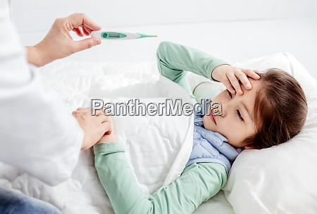 krankes kind mit grippefieber im bett