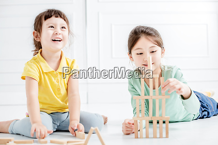 gluecklich zwei kleine maedchen spielen mit