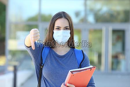 student traegt eine maske gestikulieren daumen