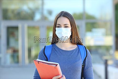 student traegt eine maske zu fuss