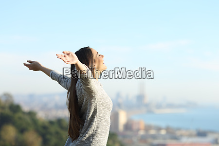 happy woman stretching arms breathing fresh