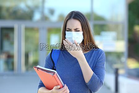 kranker student mit einer maske husten