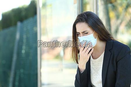 infizierte frau traegt eine maske husten