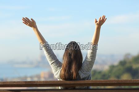 happy woman raising arms looking at