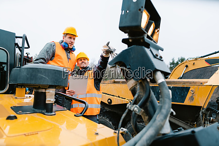 two male workers on excavator in