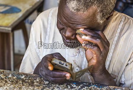 sudanesen mann reparatur eines mobiltelefons kerma