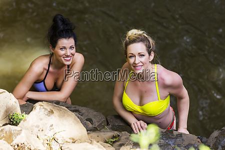 two women wearing bikinis standing in