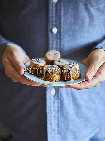 mann haelt untertasse von muffins