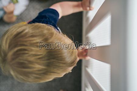 kleinkind guckt durch glastuer