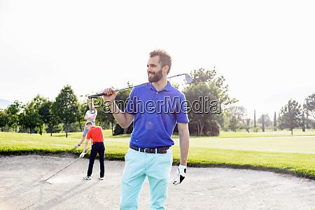 mann traegt golfschlaeger auf golfplatz freunde