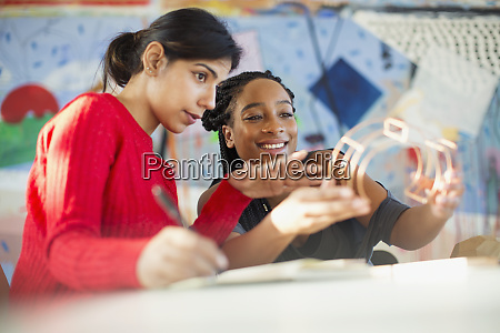 female, engineers, examining, prototype, in, office - 28124991