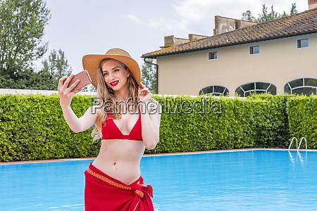 woman, in, red, bikini, taking, selfie - 28124018