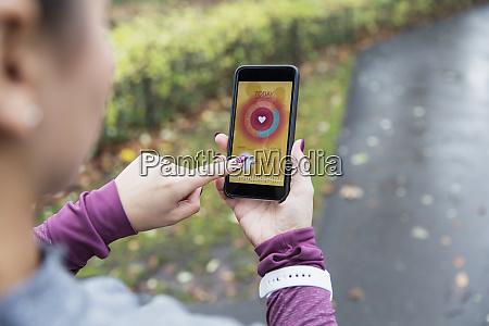 weibliche laeuferin ueberprueft herzfrequenzmesser auf smartphone