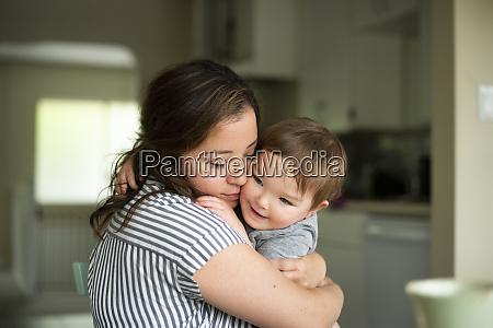 affectionate mutter umarmt kleinkind tochter