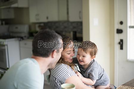 glueckliche junge familie in der kueche