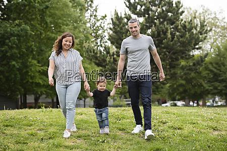 portraet glueckliche junge familie zu fuss