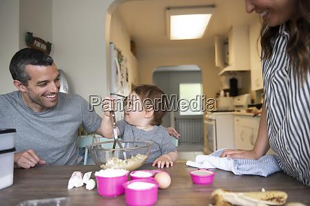 glueckliche junge familie backen am kuechentisch