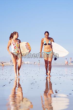 junge surferinnen mit surfbrettern am sonnigen