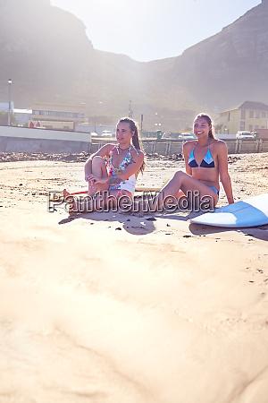 junge surferinnen entspannen am sonnigen strand