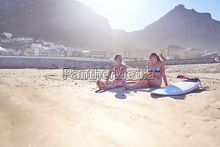 junge surferinnen freundeen sich mit surfbrettern