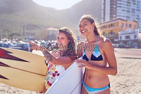 glueckliche junge surferinnen mit surfbrettern am